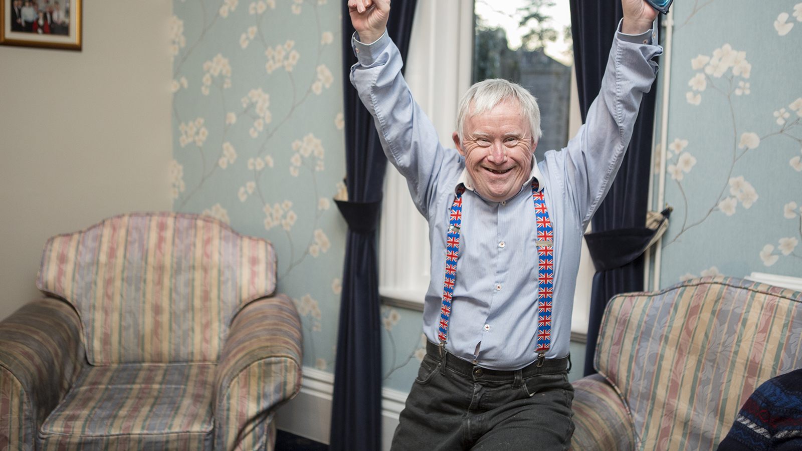 Older man stood in living room smiling with his arms raised in the air in celebration.