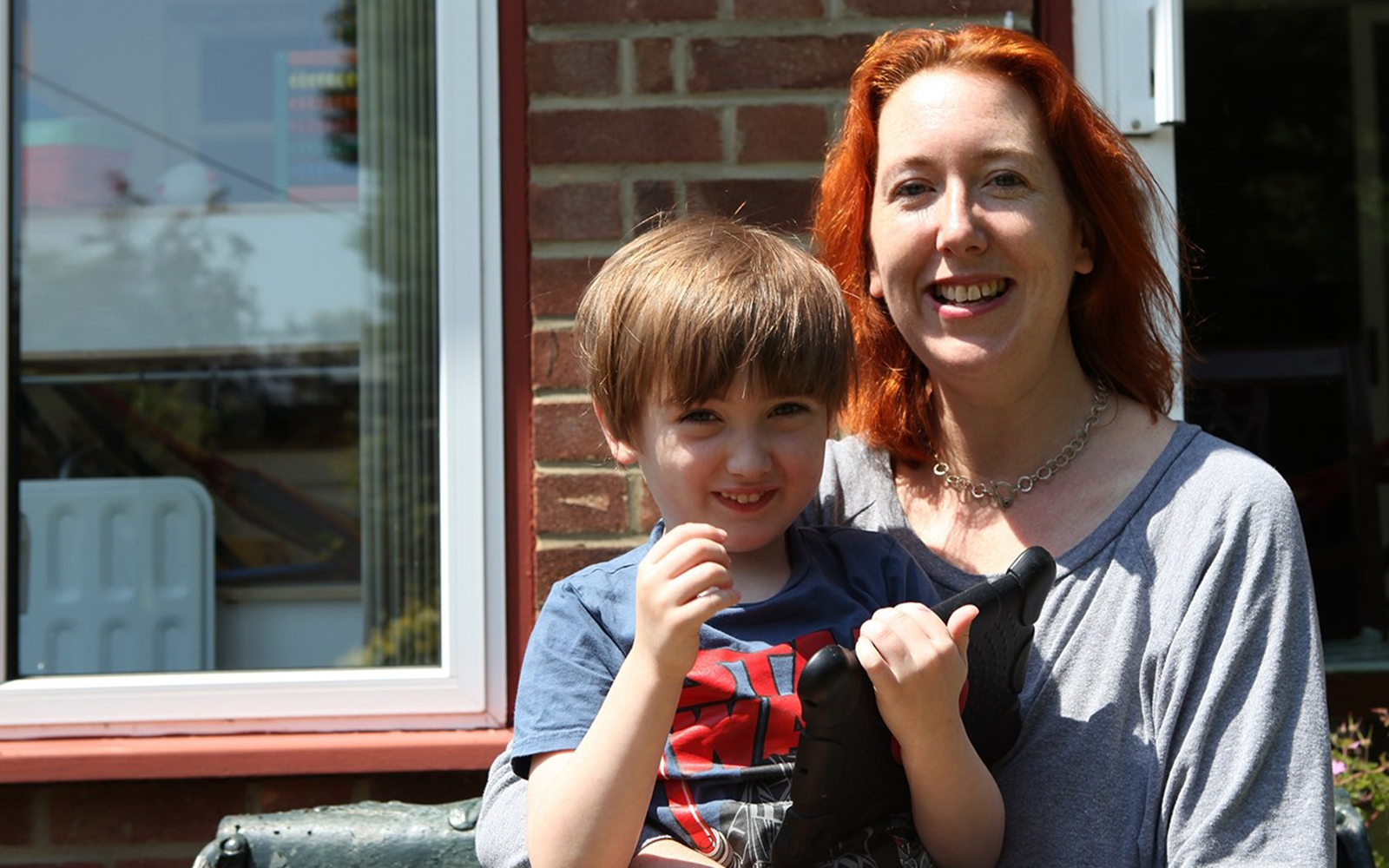 Woman sat outside in front of house with young son sat on her lap.