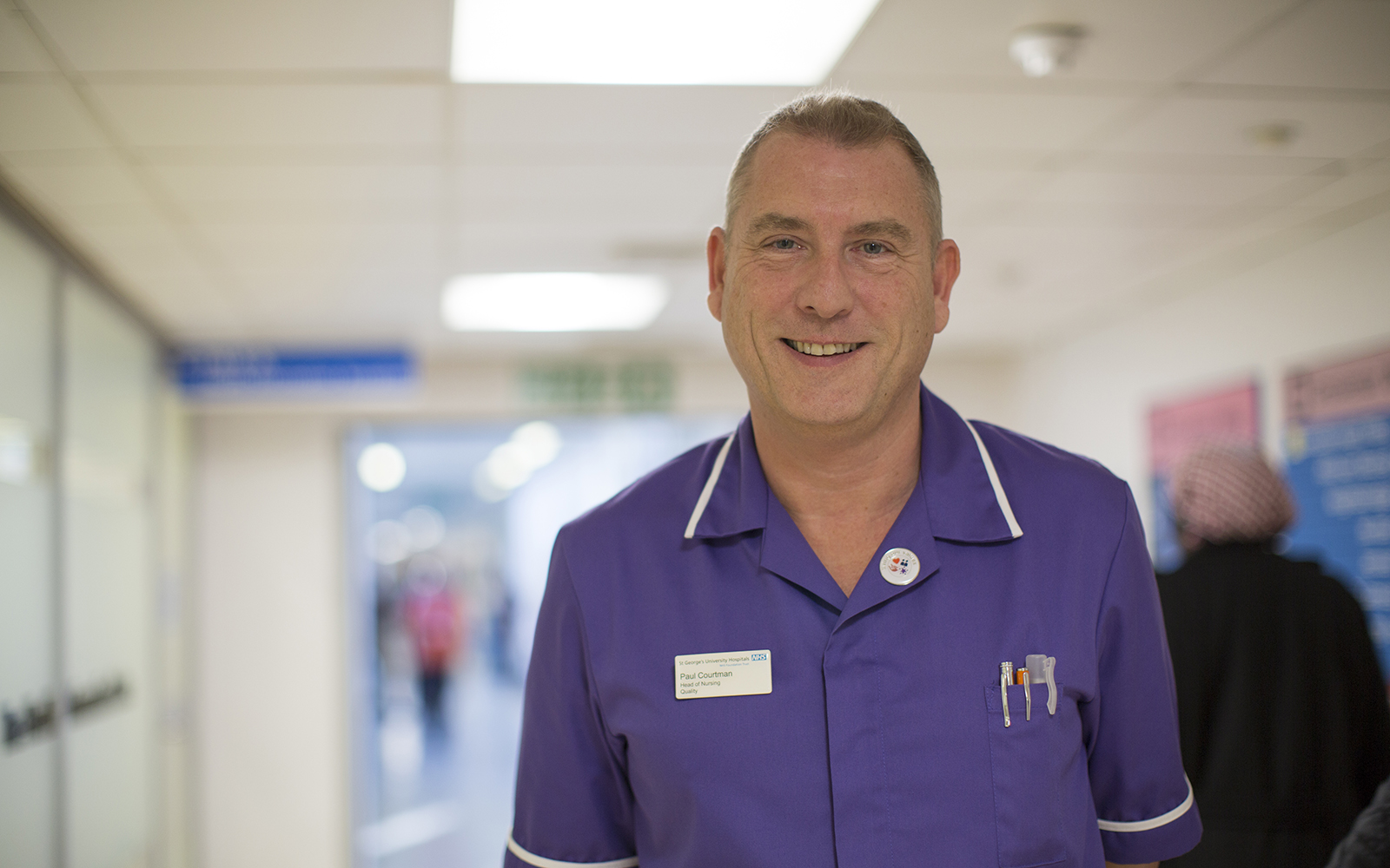 Male nurse stood smiling in hospital corridor