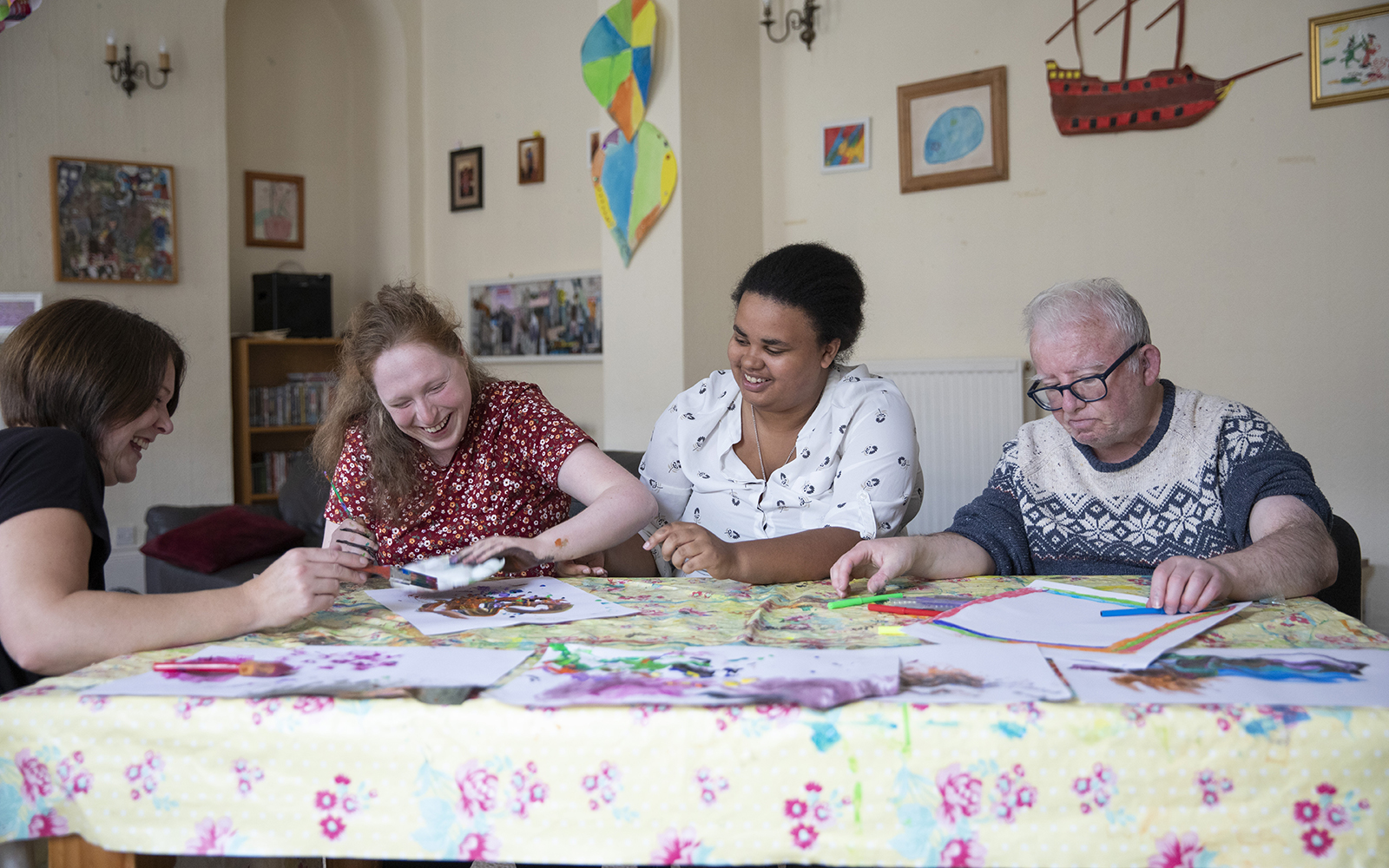 Four people sat together at kitchen table taking part in crafting activities.