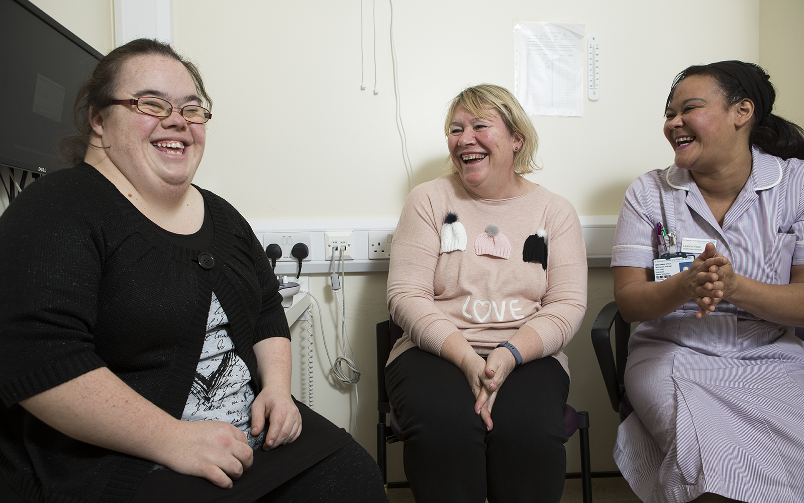 Three people sat together in doctors waiting room, smiling and laughing togther.