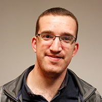 Portrait photograph of young man, Sam Jefferies, with short hair and glasses, wearing a dark green polo shirt and overcoat, smiling into camera.
