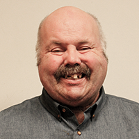 Portrait photograph of older man, Dave Taylor, with grey moustache, wearing a grey shirt, smiling into camera.