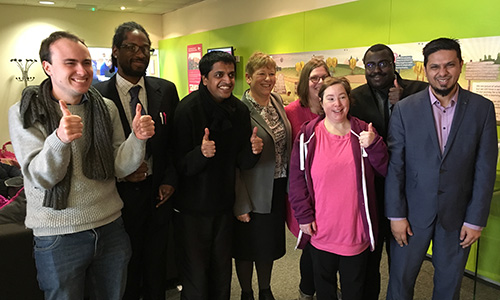 Group of people stood together inside an office, giving the thumbs up sign