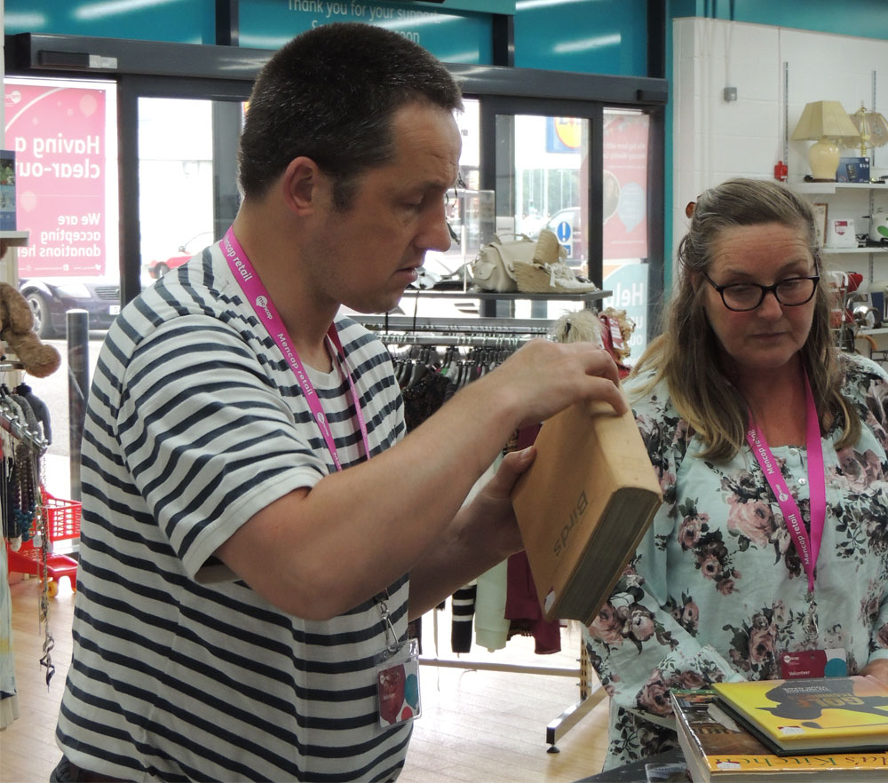 John sorting some books in a Mencap charity shop