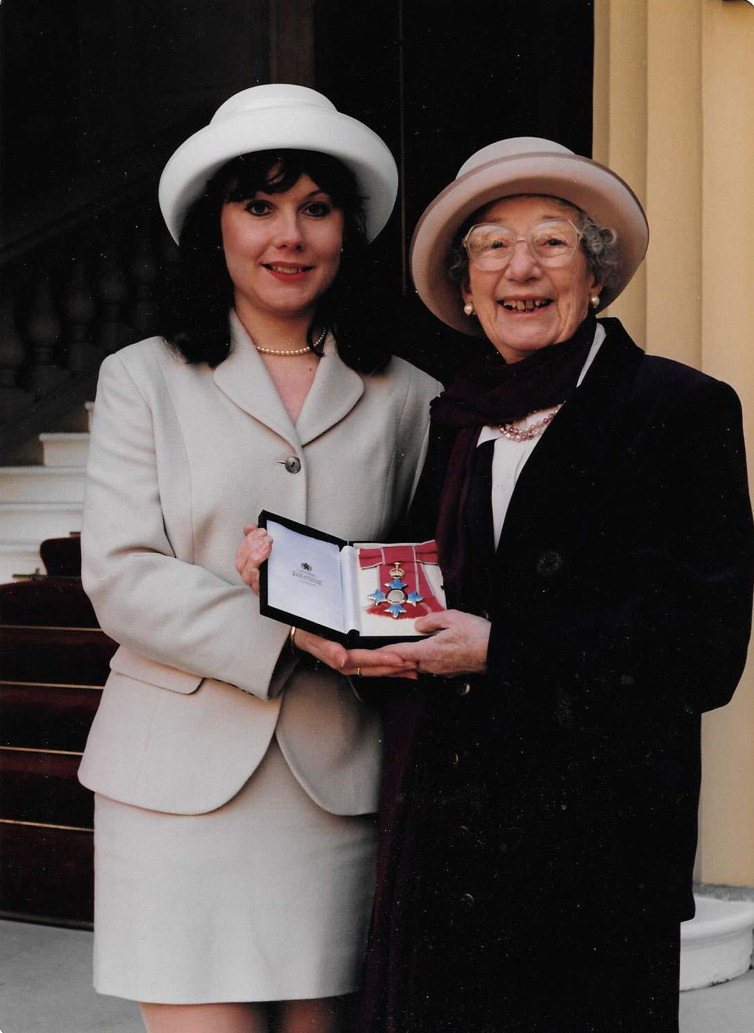 Two women stood together outside holding a box with a medal in it