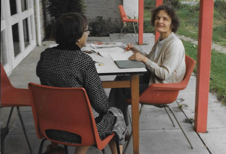 Two women sat outside at a table