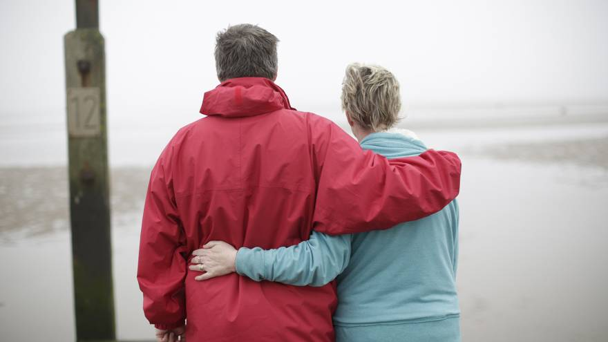 Man and woman couple with their arms around each other stood on a beach with their backs to the camera