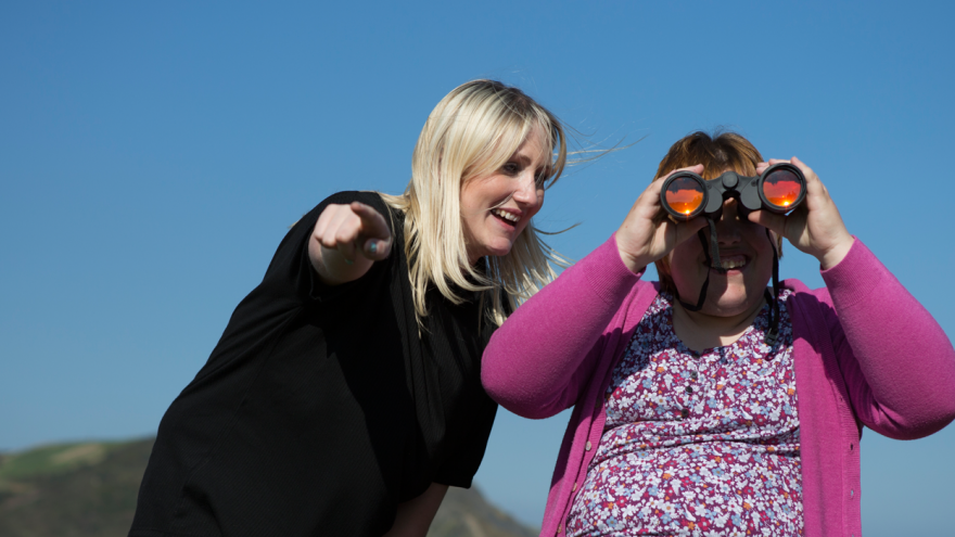 Two woman outside stood outside together on a sunny day with blue skies, woman on the right is looking through binoculars