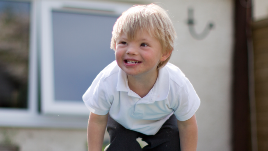 Smiling young boy with blonde hair, wearing school uniform, playing outside.
