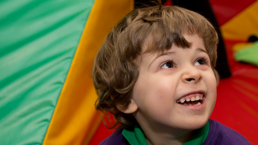 Young boy in colourful soft play area smiling upwards to the camera