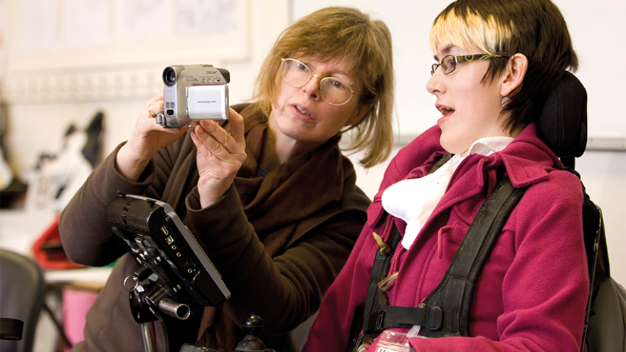 Young woman in a wheelchair being shown a video camera by another woman stood next to her
