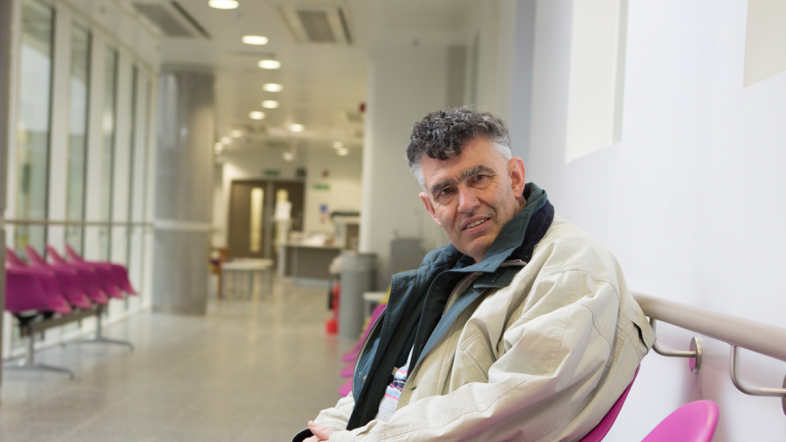 Older man wearing an overcoat sat in hospital waiting room