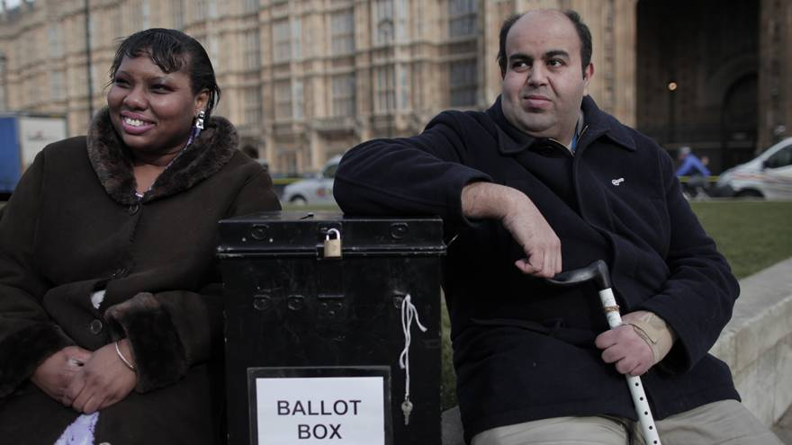 A man and a lady outside Parliament with a ballot box