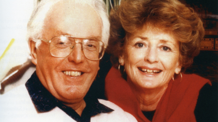 Photo of Brian Rix smiling and posing for photograph with woman next to him.
