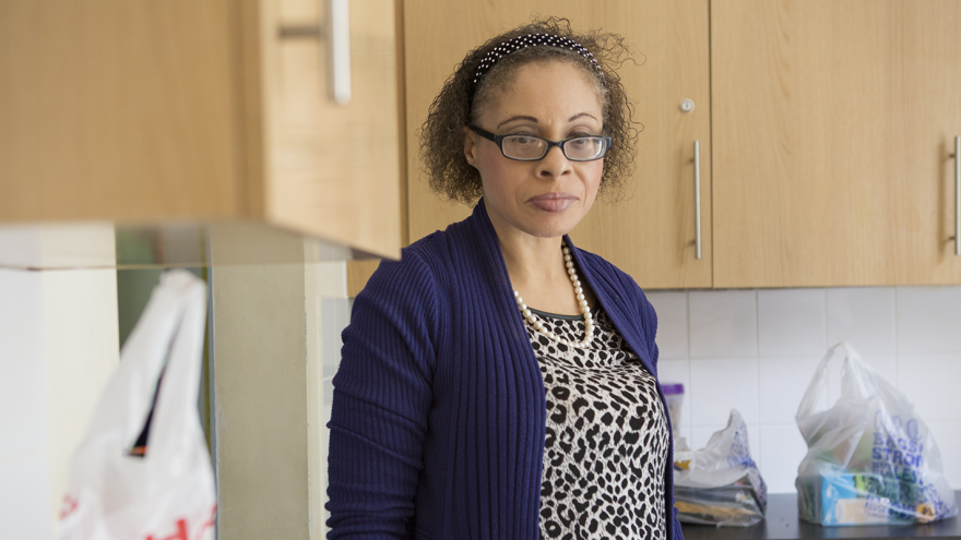 Woman wearing glasses stood in kitchen with shopping bags on counter next to her