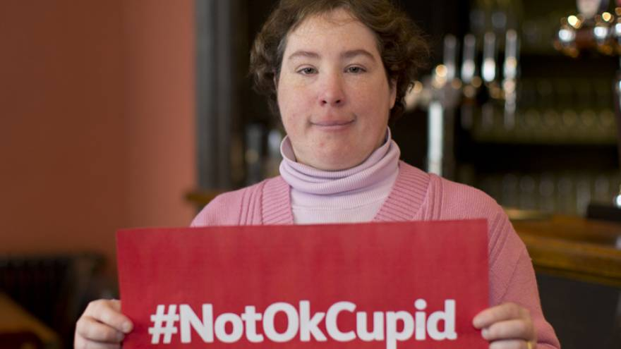 Woman holding Not OkCupid sign
