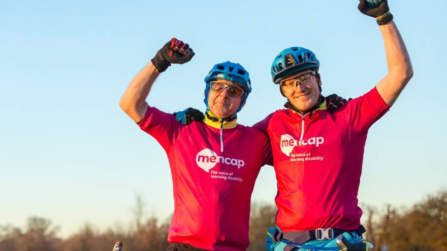 Two men on bikes holding their arms up in celebration