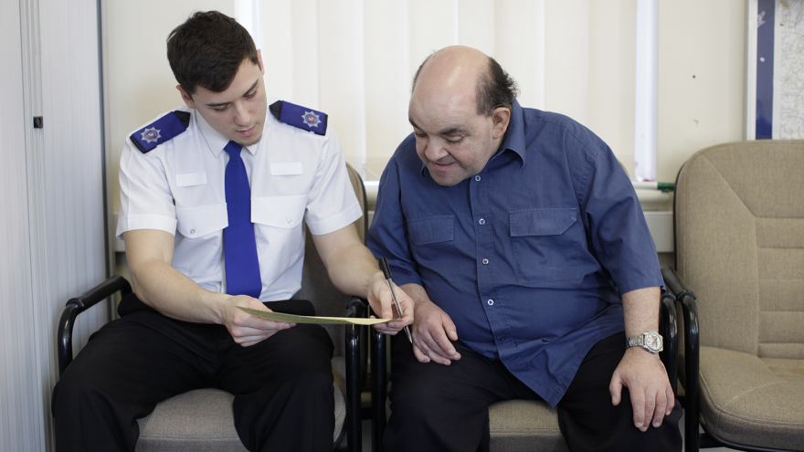 Man sat with police officer looking at paperwork