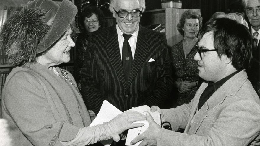 Black and white photo of Lord Rix stood behind two people who are shaking hands.