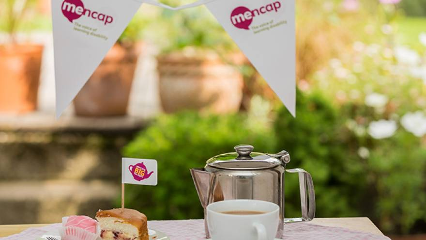Teacup and cake on a table outside with bunting in background for a tea party