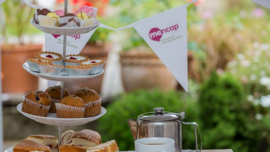 Cake stand with cakes and bunting on a table outside