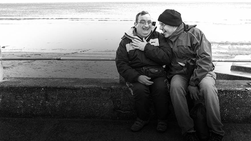 Two men laughing together, sat on a wall by the sea
