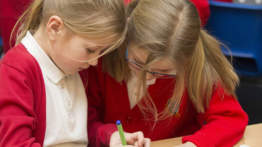Two schoolchildren working on a craft activity together