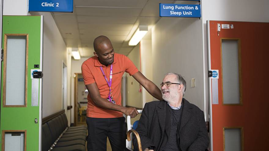 Male hospital worker pushing old man in a wheelchair through a hospital corridor