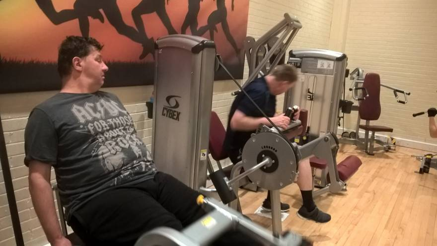 Two men using gym equipment