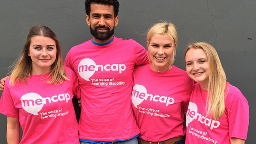 Group of four people wearing pink Mencap t-shirts stood together in front of grey wall