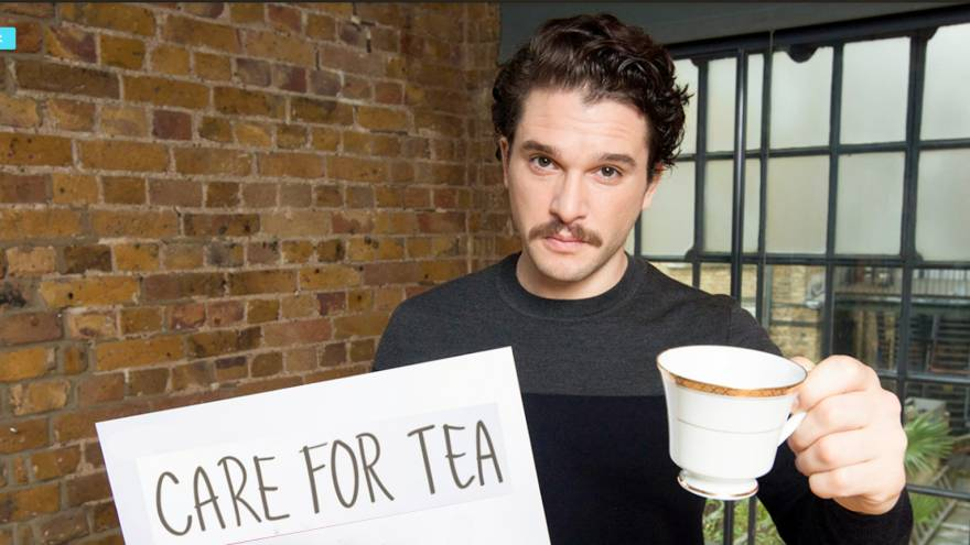 Kit Harington holding a tea cup and sign