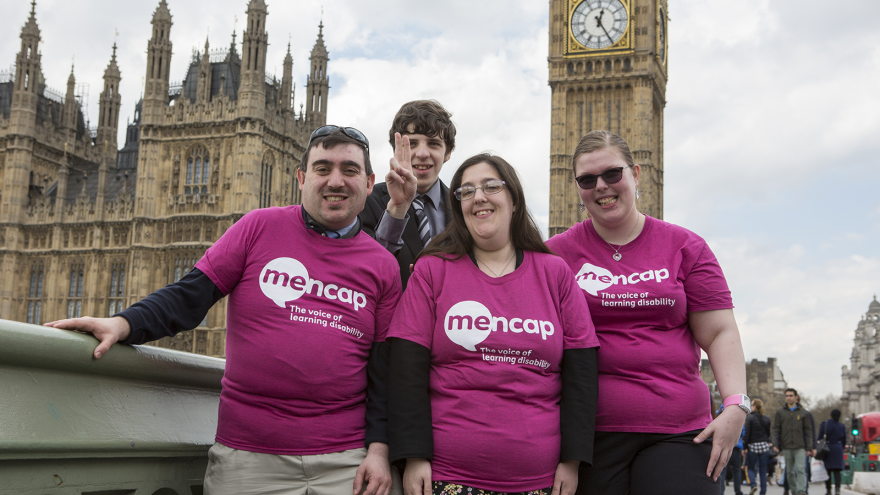 Four people wearing Mencap t-shirts stood together smiling and laughing in front of the Houses of Parliament in London.