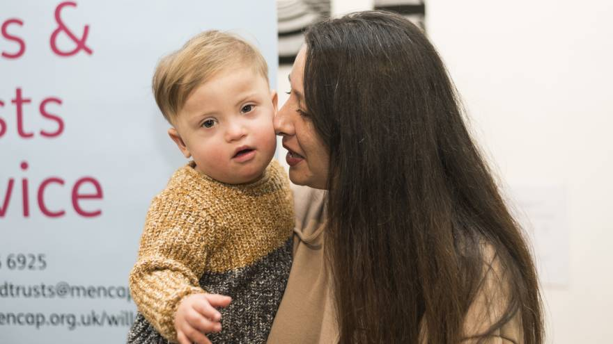 Woman with long dark hair holding her son, who is looking at the camera.