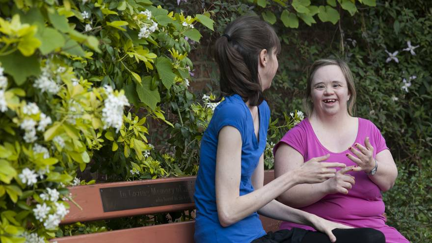 Two friends sat on park bench using Makaton signs to communicate