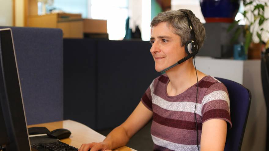 Woman with short grey hair wearing a striped purple stop sat at computer on desk in office. She is smiling and wearing a telephone headset.