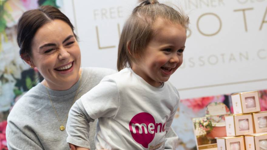 Woman laughing holding on to a young child who is also laughing and wearing a Mencap t-shirt.