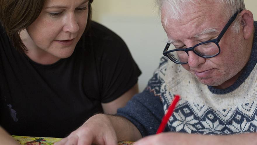 Woman sat at table with older man doing craft activities together