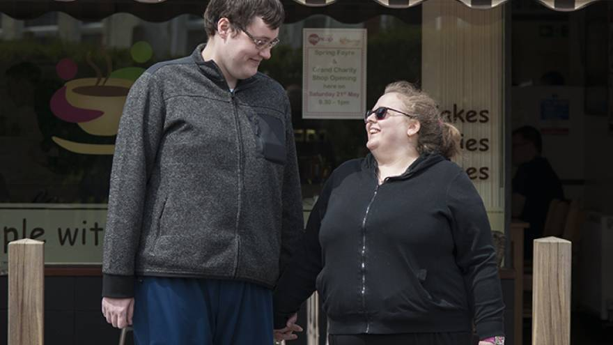 Man and woman stood outside cafe holding hands and looking at each other.