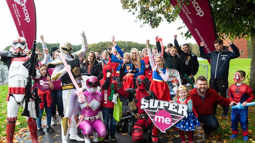 Group of parents and children stood cheering in park, many of them are dressed in fancy dress outfits as superheroes.