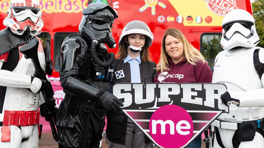 "Three people dressed as stormtroopers, with two woman stood in the middle holding a sign that says ""Super Me""."