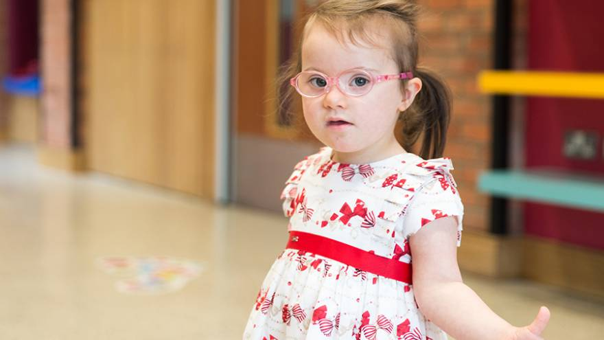 Young girl with brown hair wearing white and red dress and glasses looking into camera.