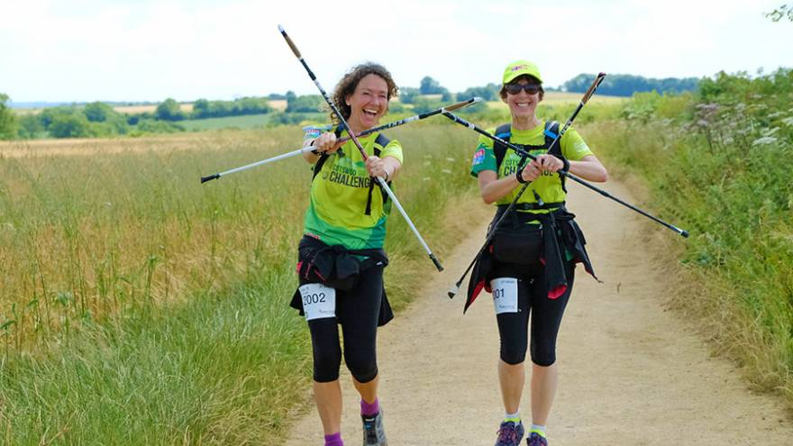 Two women walking through countryside holding walking poles in front of them.