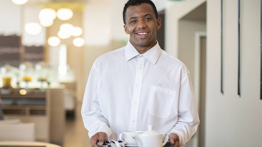Young man wearing white shirt and holding tray stood in restaurant smiling into camera