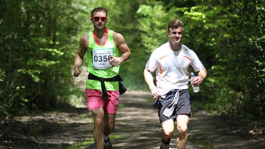 Two men running together through woodland countryside path.