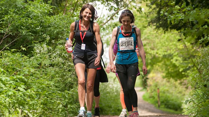 Two smiling women walking together through woodland country path.