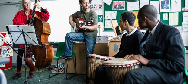 Group of four people in classroom, all playing musical instruments.