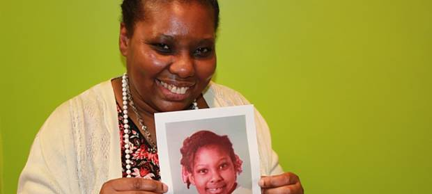 Woman stood against green background smiling and holding a photo of herself as a young girl.