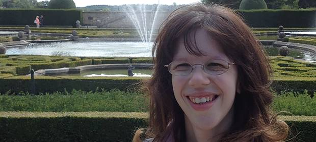 Woman with brown hair and glasses stood in park gardens in front of a water fountain, smiling into camera.