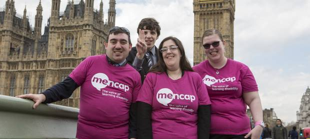 Group of four people stood together wearing Mencap t-shirts, in front of the Houses of Parliament